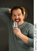 Купить «Outrageous man with mustache sing into microphone in studio with lamp on wall», фото № 25837041, снято 15 марта 2015 г. (c) Losevsky Pavel / Фотобанк Лори