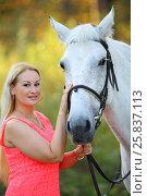 Купить «Woman in pink dress stands near on white horse in autumn park, focus on horse», фото № 25837113, снято 24 сентября 2015 г. (c) Losevsky Pavel / Фотобанк Лори