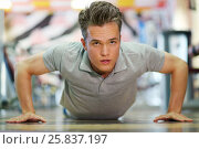 Купить «Young handsome man in shirt pressing on floor in fitness club», фото № 25837197, снято 20 июня 2015 г. (c) Losevsky Pavel / Фотобанк Лори