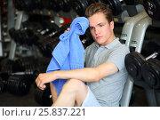 Купить «Man relaxing with towel in his hand near dumbbell rack in fitness club», фото № 25837221, снято 20 июня 2015 г. (c) Losevsky Pavel / Фотобанк Лори