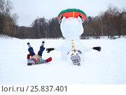 Купить «Boy lies near upside down snowman with snowtube at winter day», фото № 25837401, снято 31 января 2015 г. (c) Losevsky Pavel / Фотобанк Лори