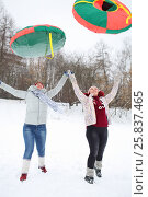 Купить «Two happy women throw up bright snow tubes outdoor at winter day», фото № 25837465, снято 31 января 2015 г. (c) Losevsky Pavel / Фотобанк Лори