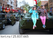 Купить «SAMARA - MAY, 6, 2015: Two girls (with model releases) pose on armored vehicle in Samara during military celebration. Red Square is not affected by military equipment on parade May 9th», фото № 25837665, снято 6 мая 2015 г. (c) Losevsky Pavel / Фотобанк Лори