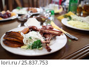 Купить «Meat ribs on plate with onions and parsley close up in cafe, Shallow dof», фото № 25837753, снято 10 мая 2015 г. (c) Losevsky Pavel / Фотобанк Лори