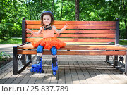 Купить «Cute little girl in blue helmet and roller skates sits on bench at summer day», фото № 25837789, снято 24 июня 2015 г. (c) Losevsky Pavel / Фотобанк Лори