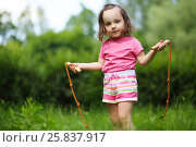 Купить «Little cute girl poses with skipping rope in summer sunny garden», фото № 25837917, снято 24 июня 2015 г. (c) Losevsky Pavel / Фотобанк Лори