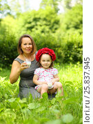 Купить «Little cute girl in flower wreath and her mother drink milk in summer park», фото № 25837945, снято 24 июня 2015 г. (c) Losevsky Pavel / Фотобанк Лори