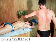 Купить «Man with broom in hand lashes back of woman lying on shelf in sauna», фото № 25837961, снято 23 марта 2016 г. (c) Losevsky Pavel / Фотобанк Лори
