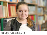 Купить «Half growth portrait of student with hair gathered in ponytail on background of shelves with books, shyly smiling at camera», фото № 25838013, снято 20 марта 2015 г. (c) Losevsky Pavel / Фотобанк Лори