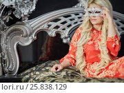 Купить «Woman with long blond hair in red dress sits on bed holding mask at face», фото № 25838129, снято 21 мая 2015 г. (c) Losevsky Pavel / Фотобанк Лори
