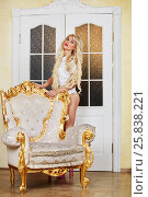 Купить «Young blonde woman stands next to the vintage gilt armchair», фото № 25838221, снято 21 мая 2015 г. (c) Losevsky Pavel / Фотобанк Лори