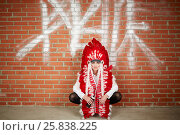Купить «Young woman dressed in costume made of red and white feathers sits squatted with her back to the brick wall with signs and holds spray can in hand», фото № 25838225, снято 13 февраля 2015 г. (c) Losevsky Pavel / Фотобанк Лори
