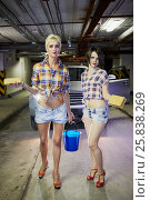 Купить «Two young girls in shorts and shirts stand in front of car with sponges and bucket with water at underground parking garage», фото № 25838269, снято 13 февраля 2015 г. (c) Losevsky Pavel / Фотобанк Лори