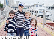Купить «Three boys in striped vests and little girl in dress stand embraced on embankment», фото № 25838313, снято 23 мая 2015 г. (c) Losevsky Pavel / Фотобанк Лори