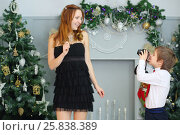 Купить «Little brother shoots his pretty sister at christmas holiday», фото № 25838389, снято 24 декабря 2014 г. (c) Losevsky Pavel / Фотобанк Лори