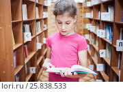 Купить «Teenage girl stands between bookcases in library and reads book», фото № 25838533, снято 26 июня 2015 г. (c) Losevsky Pavel / Фотобанк Лори