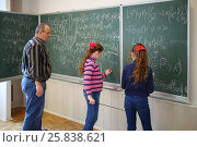 Купить «Teacher and two girls stand near blackboard with formulas in classroom, girl writes», фото № 25838621, снято 7 апреля 2016 г. (c) Losevsky Pavel / Фотобанк Лори