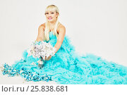 Купить «Smiling woman in blue fluffy dress with bunch of artificial flowers», фото № 25838681, снято 29 марта 2015 г. (c) Losevsky Pavel / Фотобанк Лори