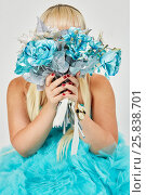 Купить «Woman in blue fluffy dress hides her face behind a bunch of artificial flowers she holds in hands.», фото № 25838701, снято 29 марта 2015 г. (c) Losevsky Pavel / Фотобанк Лори