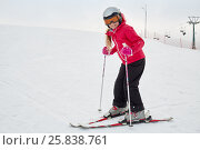 Smiling teenage girl equipped for skiing on snowy slope at ski resort. Стоковое фото, фотограф Losevsky Pavel / Фотобанк Лори