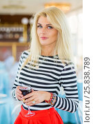 Купить «Blonde pretty woman in striped t-shirt holds glass of wine in restaurant», фото № 25838789, снято 25 августа 2015 г. (c) Losevsky Pavel / Фотобанк Лори