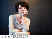 Купить «Portrait of dark-haired woman in white knitted dress, sitting and propping her chin with hand», фото № 25839249, снято 29 марта 2015 г. (c) Losevsky Pavel / Фотобанк Лори