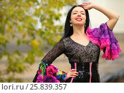 Купить «Young woman in beautiful bright costume poses outdoor and smiles», фото № 25839357, снято 15 октября 2015 г. (c) Losevsky Pavel / Фотобанк Лори