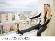 Pretty young woman in black cat costume sits on balcony at autumn day. Стоковое фото, фотограф Losevsky Pavel / Фотобанк Лори