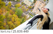 Купить «Pretty young woman in black cat costume poses on balcony at autumn day, top view», фото № 25839449, снято 15 октября 2015 г. (c) Losevsky Pavel / Фотобанк Лори