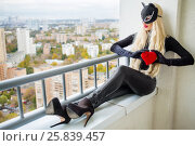 Pretty woman in black with cat ears holds red heart and sits on balcony in city. Стоковое фото, фотограф Losevsky Pavel / Фотобанк Лори
