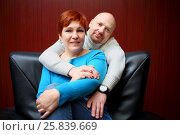 Купить «Portrait of a bald man and a red-haired woman sitting on black leather chair», фото № 25839669, снято 21 февраля 2015 г. (c) Losevsky Pavel / Фотобанк Лори