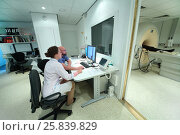 Купить «RUSSIA, MOSCOW - AUG 31, 2015: two experienced physicians in control room, and magnetic resonance imaging machine with patient», фото № 25839829, снято 31 августа 2015 г. (c) Losevsky Pavel / Фотобанк Лори