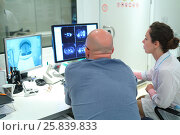 Купить «RUSSIA, MOSCOW - AUG 31, 2015: Experienced doctor and her assistant looking at MRI scan on Monitor in control room multidisciplinary Clinic Center Endosurgery and Lithotripsy (CELT), view from back», фото № 25839833, снято 31 августа 2015 г. (c) Losevsky Pavel / Фотобанк Лори
