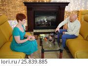 Купить «A woman in a green dress looks like a man pours wine into glasses», фото № 25839885, снято 22 февраля 2015 г. (c) Losevsky Pavel / Фотобанк Лори
