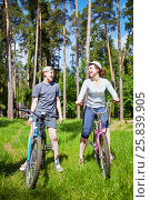 Купить «Mother and son on bicycles stand at grassy lawn in pine forest», фото № 25839905, снято 30 мая 2015 г. (c) Losevsky Pavel / Фотобанк Лори