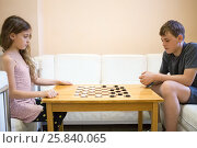 Купить «Boy and girl play checkers on chess table in room», фото № 25840065, снято 30 мая 2015 г. (c) Losevsky Pavel / Фотобанк Лори