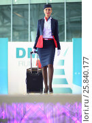 Купить «MOSCOW – JUL 09, 2015: A woman with suitcase shows a gray uniforms flight attendant at a special screening of uniforms airlines DME RUNVAY in Domodedovo», фото № 25840177, снято 9 июля 2015 г. (c) Losevsky Pavel / Фотобанк Лори