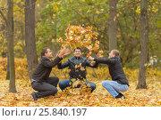 Купить «Three men in black jackets hunker down and pop-up yellow maple leaves in park», фото № 25840197, снято 25 октября 2015 г. (c) Losevsky Pavel / Фотобанк Лори