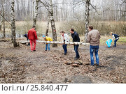 Купить «MOSCOW, RUSSIA - APR 18, 2015: People carry big tree trunk during cleaning works at Elk Island residential complex. More than 2.5 million people participate in annual cleaning work in Moscow.», фото № 25840477, снято 18 апреля 2015 г. (c) Losevsky Pavel / Фотобанк Лори