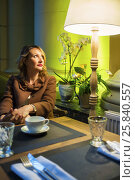 Купить «Middleaged pretty woman sits with tea and looks up in cozy restaurant», фото № 25840557, снято 12 июля 2015 г. (c) Losevsky Pavel / Фотобанк Лори