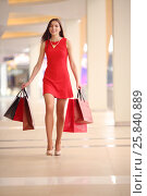 Купить «Pretty young woman in red dress goes with bags and smiles in shopping center», фото № 25840889, снято 21 апреля 2015 г. (c) Losevsky Pavel / Фотобанк Лори
