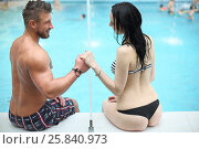 Купить «Tanned man and light-skinned woman in swimwear holding hands and looking at each other sitting by the pool, view from the back», фото № 25840973, снято 28 февраля 2015 г. (c) Losevsky Pavel / Фотобанк Лори