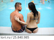 Купить «Tanned man and light-skinned woman in swimwear looking at each other sitting by the pool, view from the back», фото № 25840985, снято 28 февраля 2015 г. (c) Losevsky Pavel / Фотобанк Лори