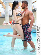 Купить «Enamoured man and woman looking at each other in pool at the aquapark», фото № 25841021, снято 28 февраля 2015 г. (c) Losevsky Pavel / Фотобанк Лори