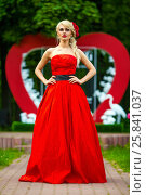 Portrait of beautiful woman in red dress in summer park standing before wedding installation. Стоковое фото, фотограф Losevsky Pavel / Фотобанк Лори