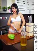 Купить «Pretty woman in underwear poses with knife near table in kitchen», фото № 25841041, снято 4 июня 2015 г. (c) Losevsky Pavel / Фотобанк Лори