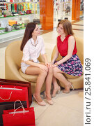 Купить «Two girls sit in leather armchairs with bags and talk in mall», фото № 25841069, снято 21 апреля 2015 г. (c) Losevsky Pavel / Фотобанк Лори