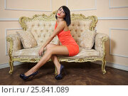 Купить «Beautiful girl in short red dress sitting on couch and posing», фото № 25841089, снято 4 июня 2015 г. (c) Losevsky Pavel / Фотобанк Лори