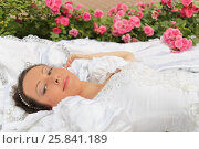 Купить «Woman in white dress lying on lawn among flowers in summer park,close-up, looking at camera and smiling», фото № 25841189, снято 16 июля 2015 г. (c) Losevsky Pavel / Фотобанк Лори