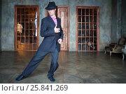 Купить «Man in suit dances tango in retro room with wooden doors and big windows», фото № 25841269, снято 4 июня 2015 г. (c) Losevsky Pavel / Фотобанк Лори